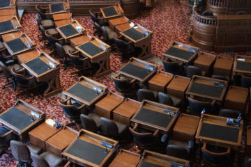 A view of the Iowa House floor from above. The carpet is a red flower pattern and the desks are wood.