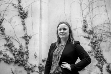 A black and white image of Emily Barske, a young white woman with shoulder-length brown hair. She is wearing a black blazer and a dark shirt and is standing in front of a wall covered with vines.