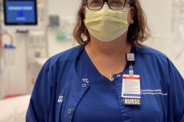 A woman with glasses and medium-length brown curly hair wears blue scrubs and a yellow face mask.