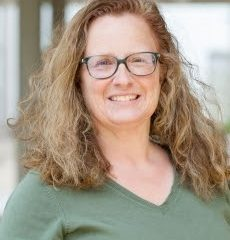 A woman with glasses and light brown curly hair wearing a green v-neck shirt smiles at the camera