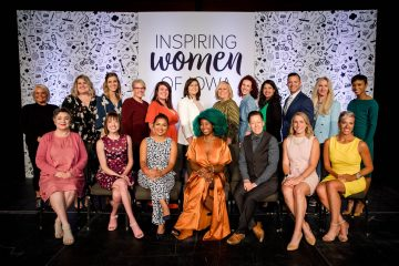 """A diverse group of people posing for a group picture against background that reads """"Inspiring Women of Iowa"""""""